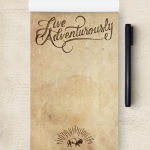 "A custom notepad reading ""live adventurously""."