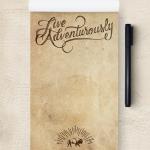 "A custom notepad reading ""live adventurously""."