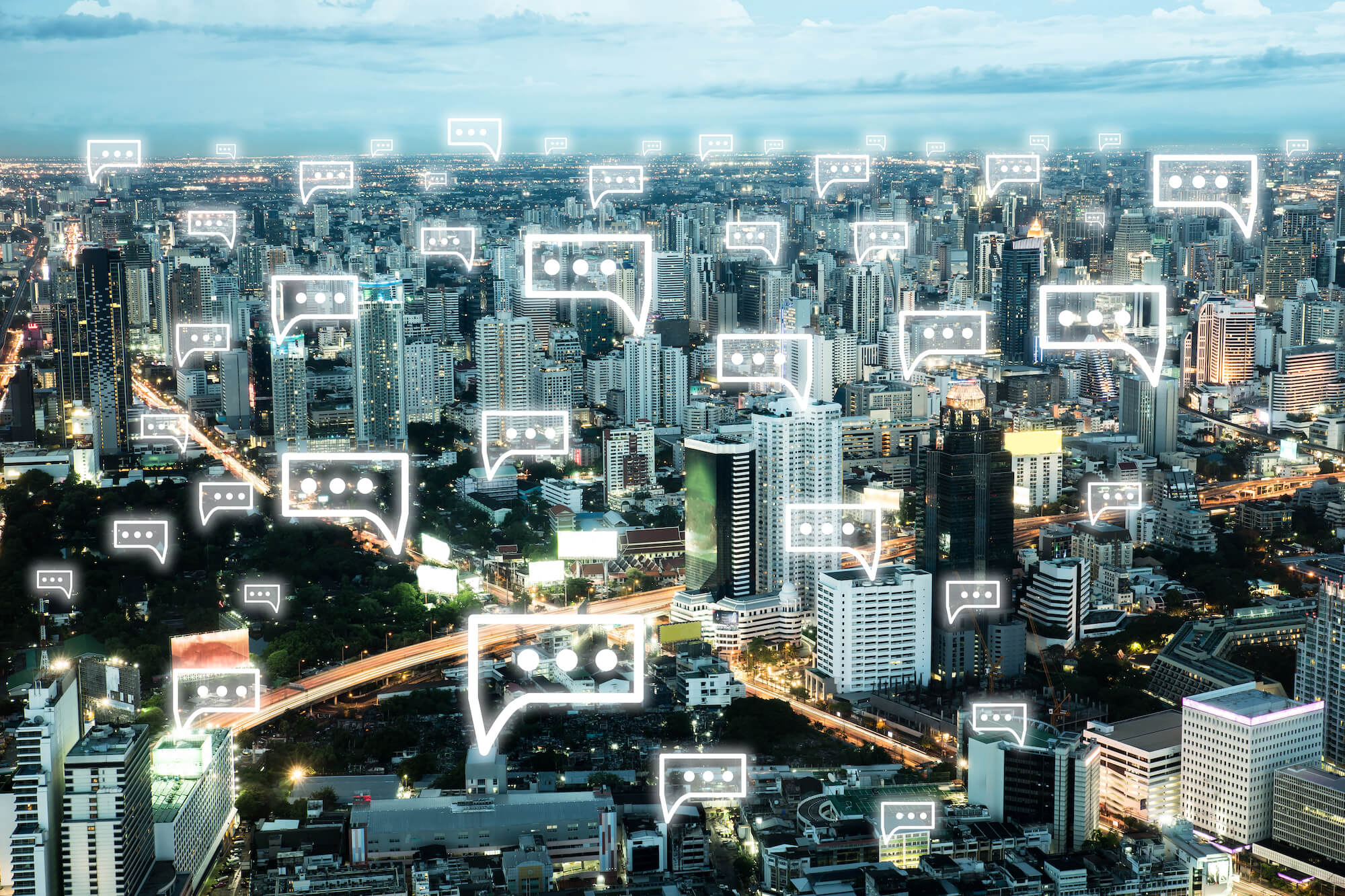 A view of a city, with chat messaging bubbles displaying over the buildings.